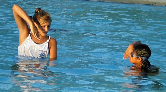 Swim instructor with young student in the pool